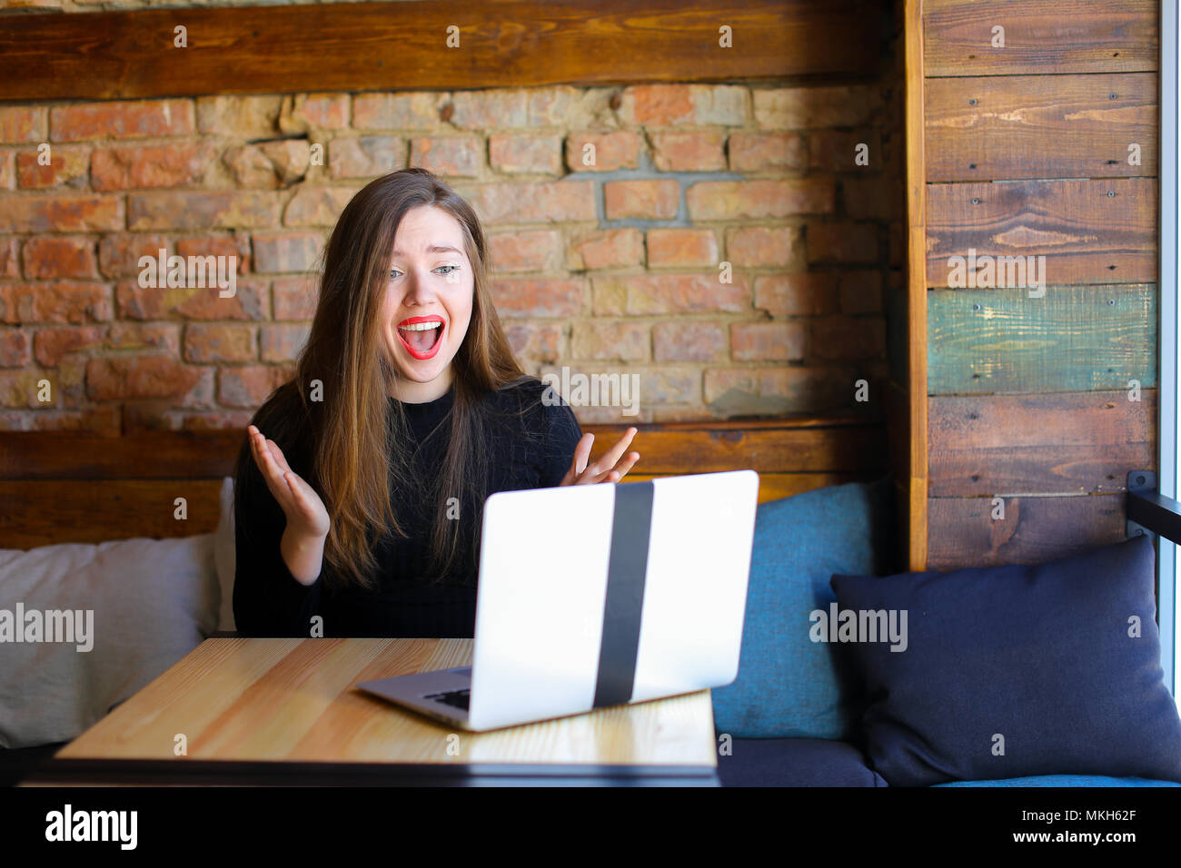 Shocked and disappointed female person using laptop and sitting at cafe. - Stock Image