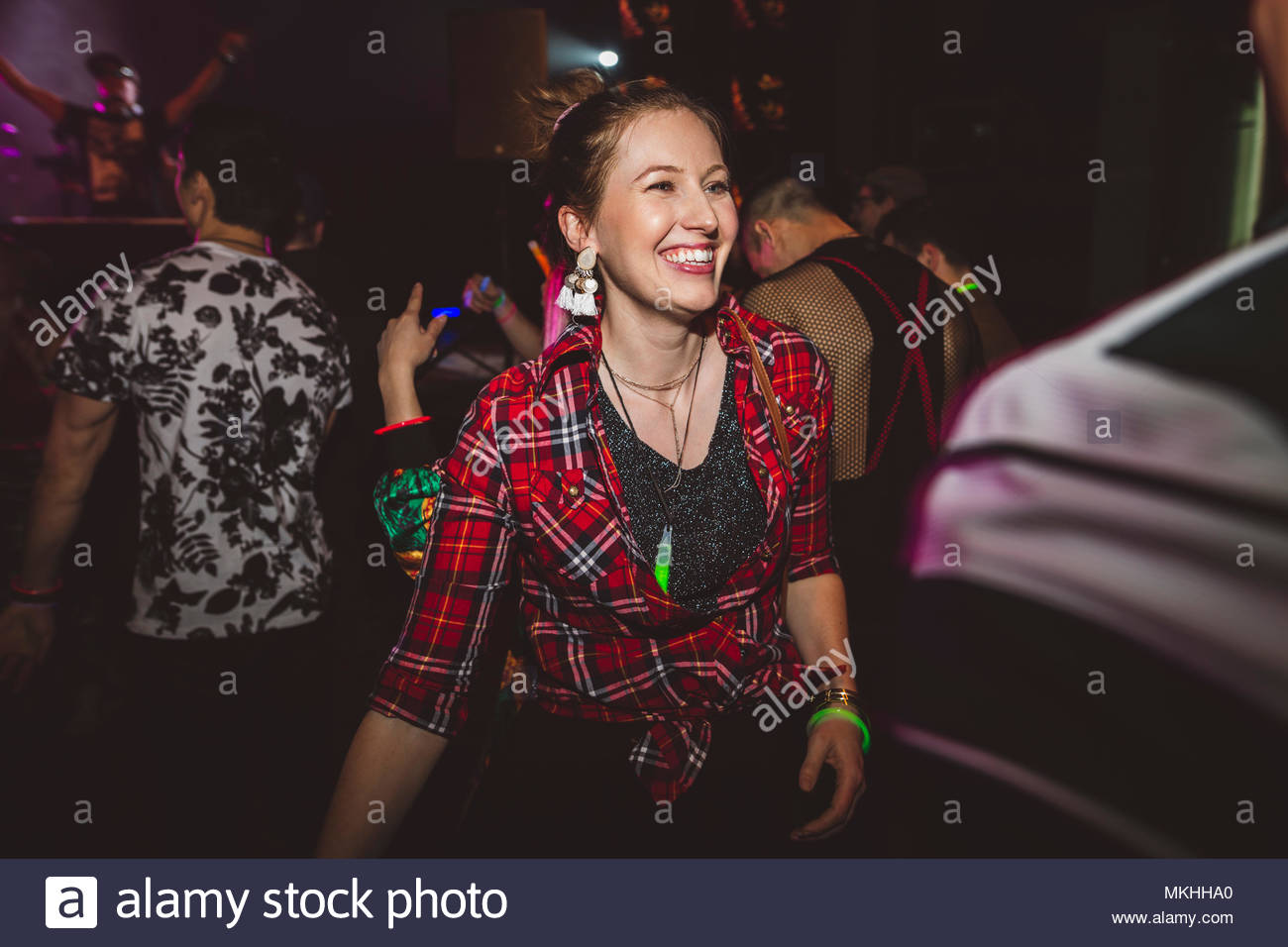 Confident, happy female millennial partying in nightclub - Stock Image