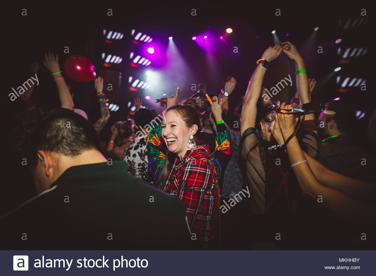 Female millennial laughing, partying and dancing in nightclub - Stock Image