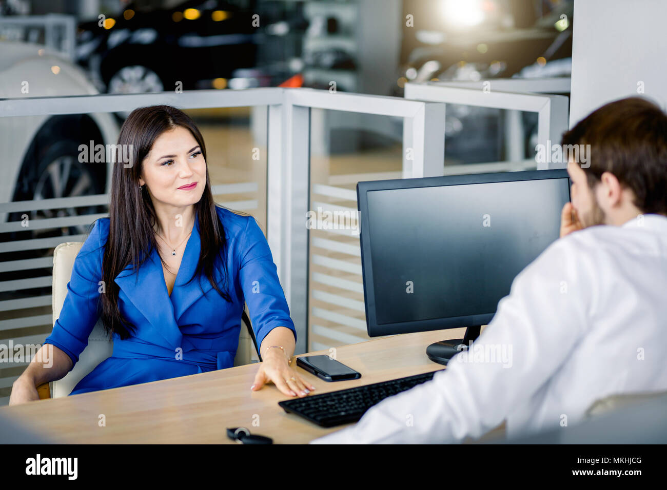 Young caucasian couple of honeymooners taking decision of buying a car in the car deaker office - Stock Image