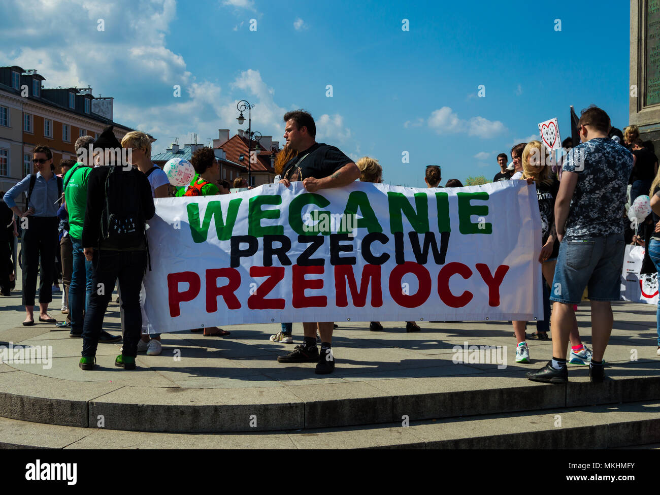 Vegan manifestation for animal rights in the Warsaw's Castle Square. Activists hold a sign with the phrase 'Vegans against violence'. - Stock Image