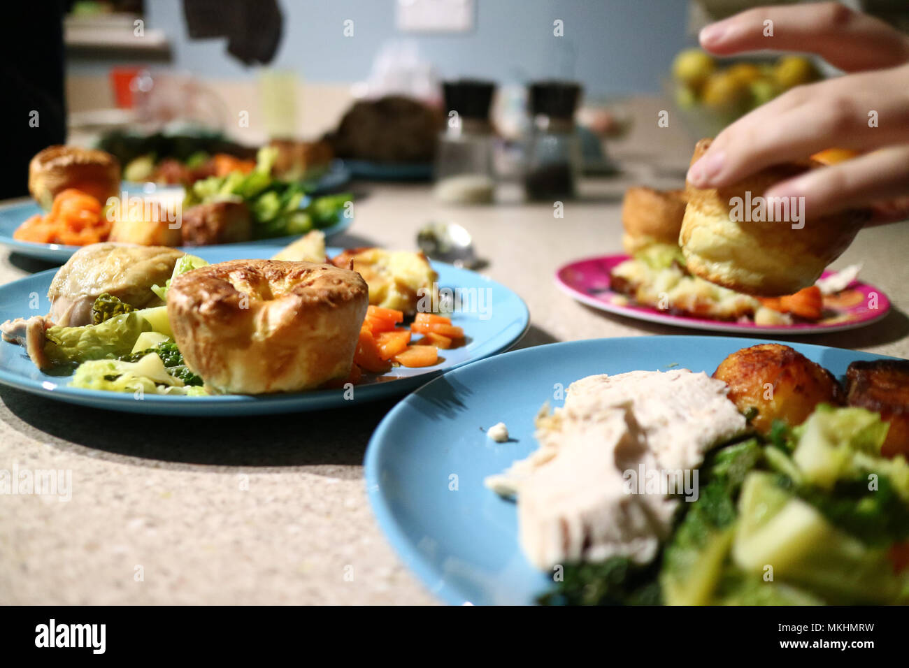 Roast dinners ready to serve while a hand steals a Yorkshire pudding. - Stock Image