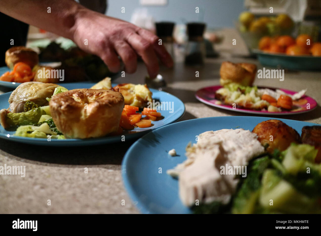 Roast dinners ready to serve while a hand places the final touch. - Stock Image