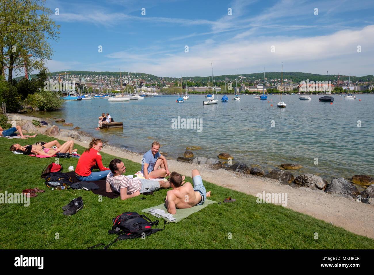 People enjoying a sunny day at Strandbad Mythenquai, on banks of Lake Zurich, Zürich, Switzerland, Europe - Stock Image