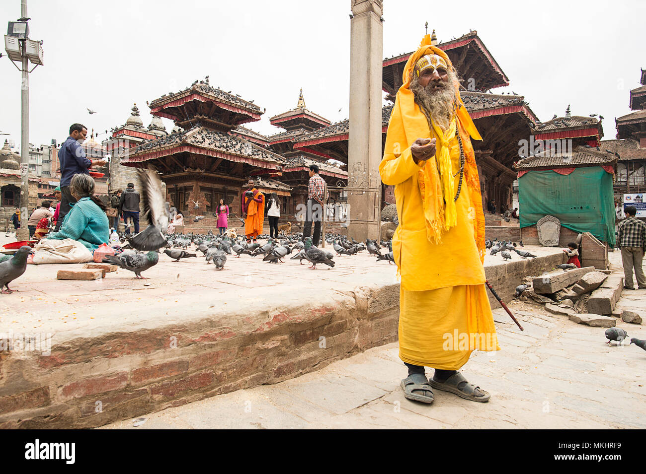 KATHMANDU - NEPAL 08 APRIL 2018. Sadhu in colourful clothes and painted face standing on Durbar Square asking for alms in Kathmandu, Nepal. Stock Photo