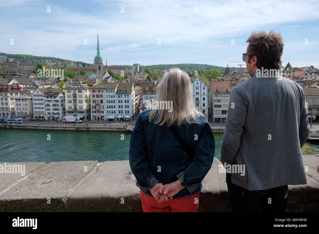 Two people looking at the skyline of Zurich from the Lindenhof hill, Switzerland, Europe - Stock Image