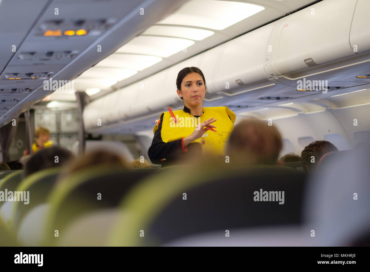 A flight attendant demonstrating inflatable life vest usage - Stock Image