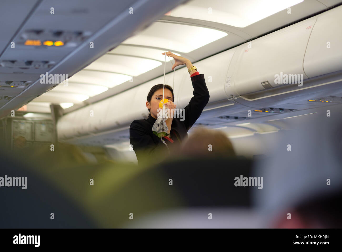 Flight hostess in uniform showing how to use the airplane's emergency oxygen mask during safety procedure demonstration - Stock Image