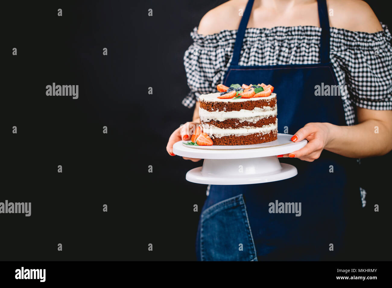 Young Woman In Denim Apron Holding Chocolate Birthday Cake With Berries Over Black Background
