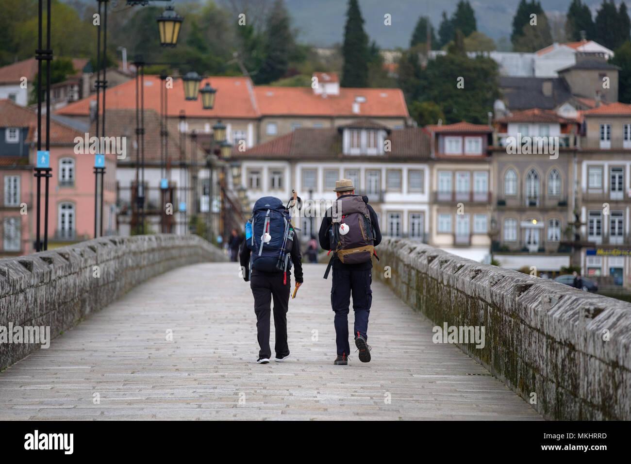 Rear view of two pilgrims heading to Santiago de Compostela using the portuguese way, Ponte de Lima, Portugal Stock Photo