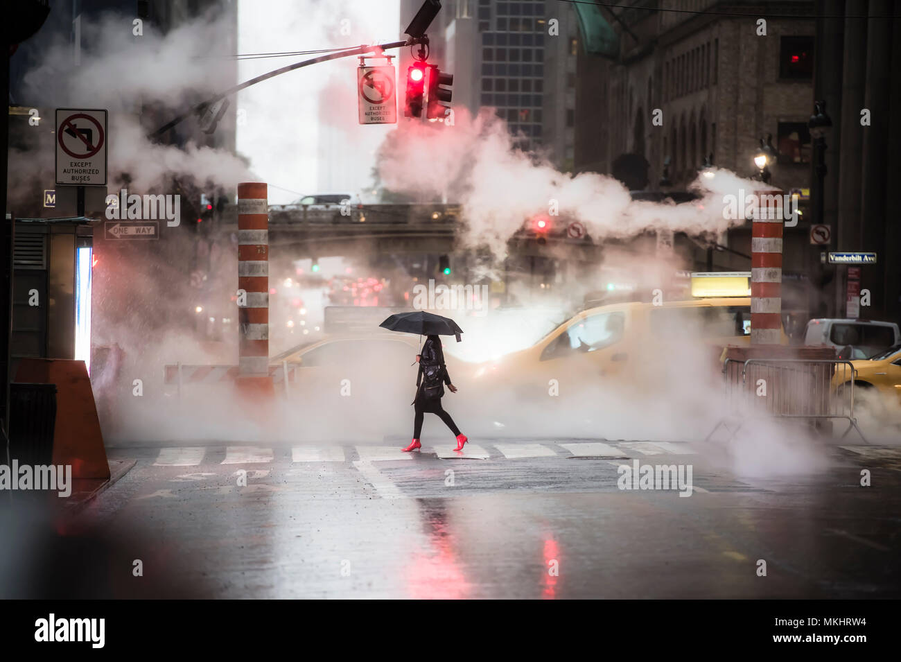 A woman with an umbrella and red high heels shoes is crossing the 42nd street in Manhattan. Taxi and steam coming out from from the manholes in the ba - Stock Image