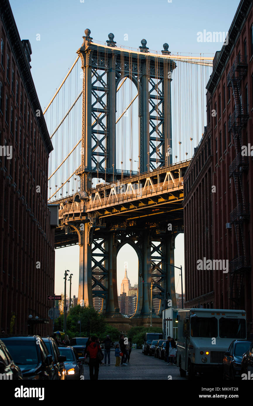 Brooklyn bridge seen from a narrow alley enclosed by two brick buildings during the sunset. New York City, USA. Stock Photo