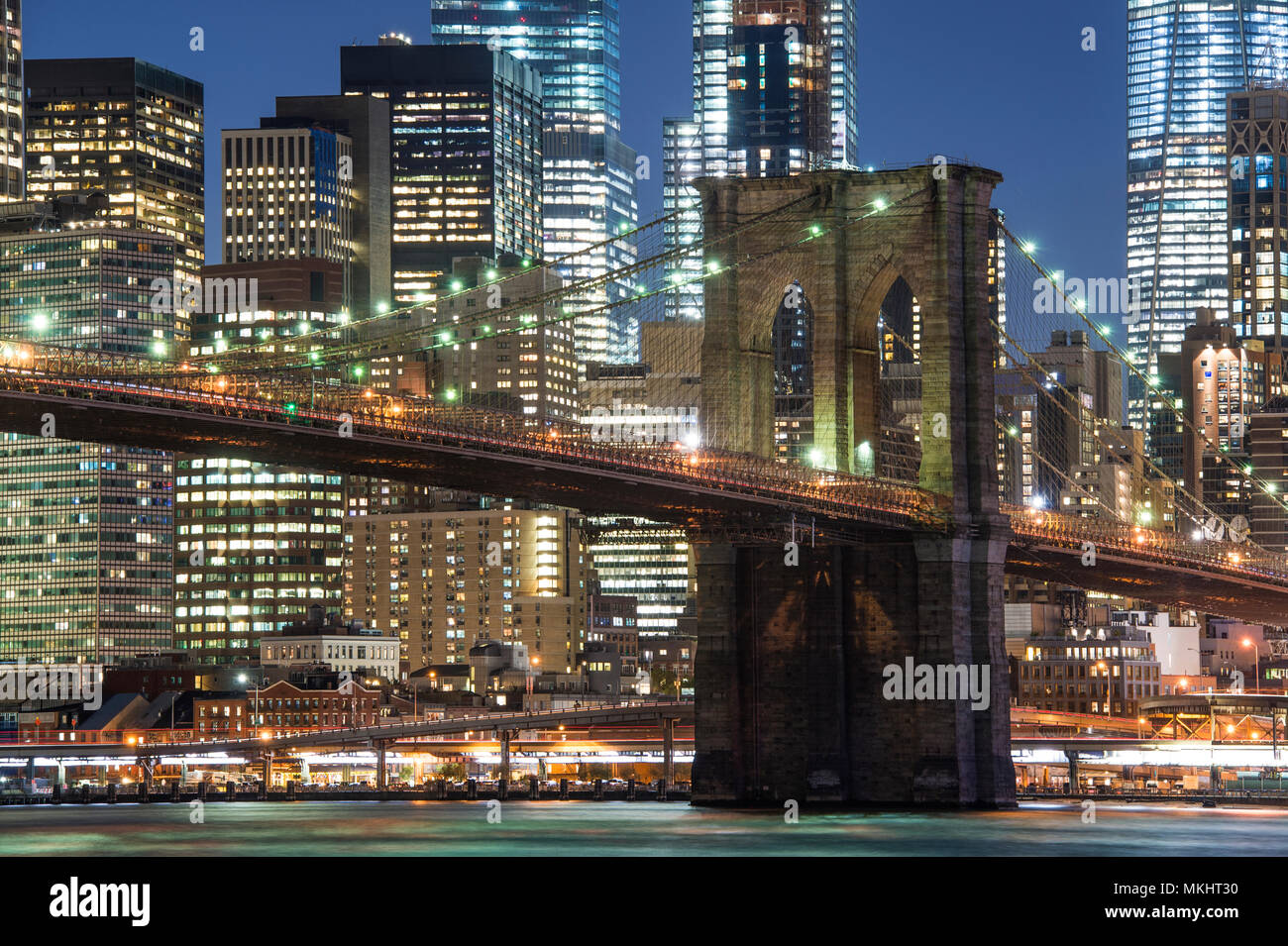 Brooklyn Bridge and the illuminated Skyline of Manhattan in the evening with blue sky and smooth water surface shot from Brooklyn side, New York, Usa. - Stock Image