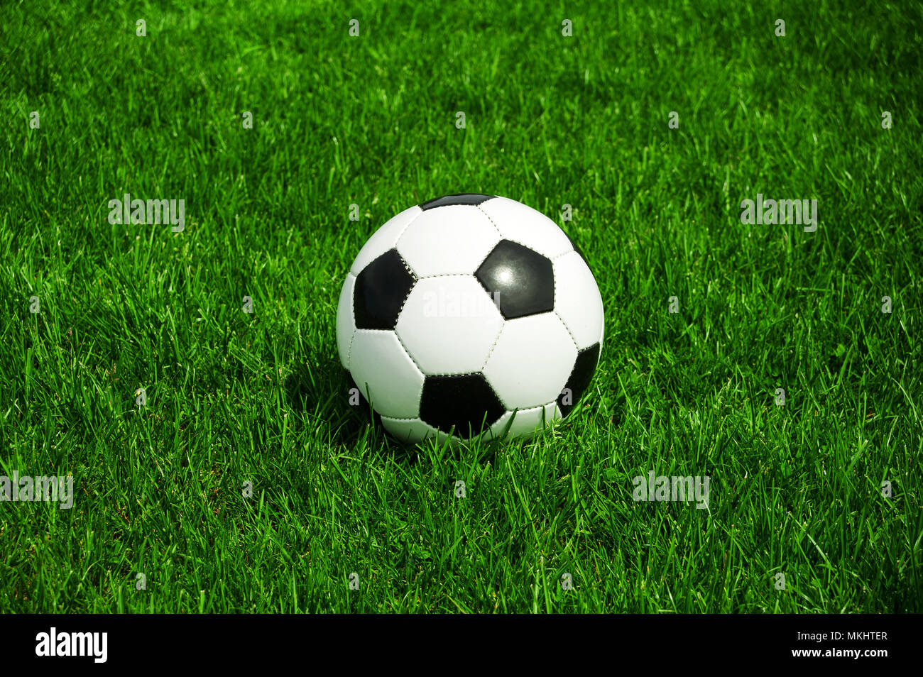 soccer ball black and white classic in the green grass alone with space - Stock Image