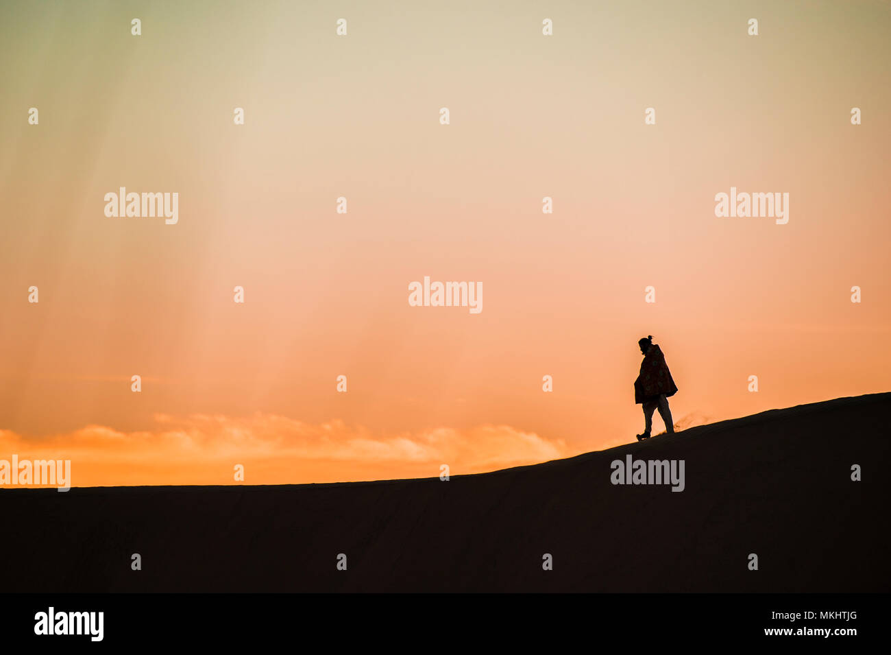 Man walk on a desert sand dunes at sunset in Rajasthan, India. Stock Photo