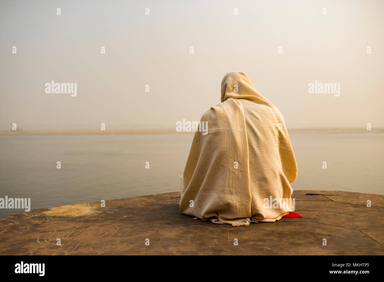 A holy man dressed in white is praying and meditating on one of the many Ghats of Varanasi in front of the sacred river Ganges, India. - Stock Image