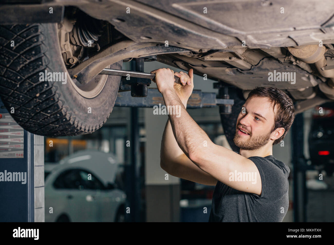 Auto mechanic working at auto repair shop under car with tool - Stock Image