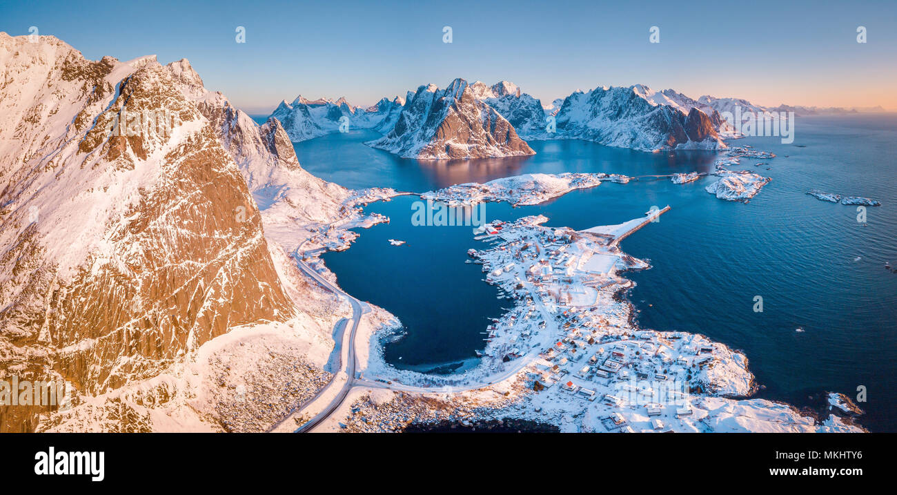 Aerial panoramic view of amazing Lofoten Islands winter scenery with famous Reine fishing village in beautiful golden morning light at sunrise, Norway - Stock Image