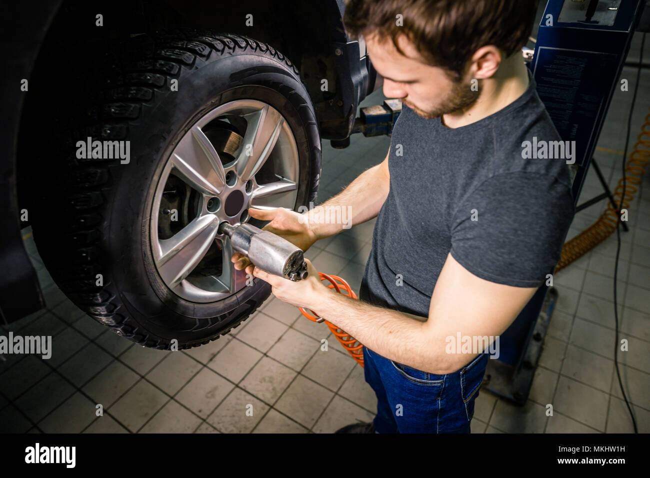 car mechanic changing car wheel in auto repair garage Stock Photo