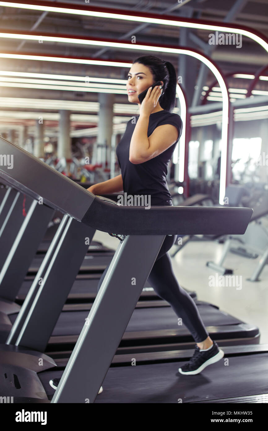 Fit business woman talking on smartphone while running on treadmill Stock Photo
