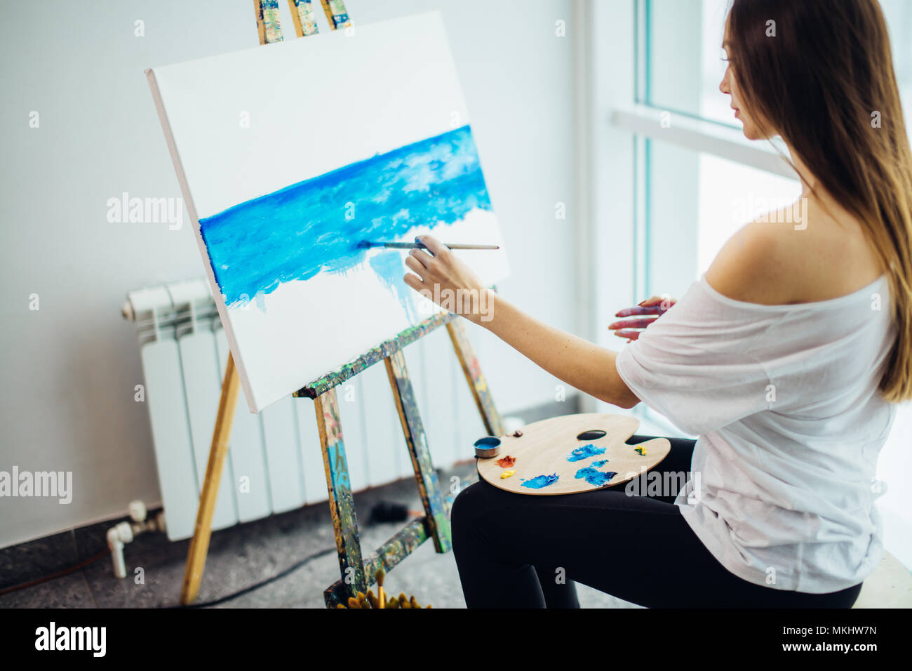 Young Attractive Woman Artist Painting Sea Scape On Canvas