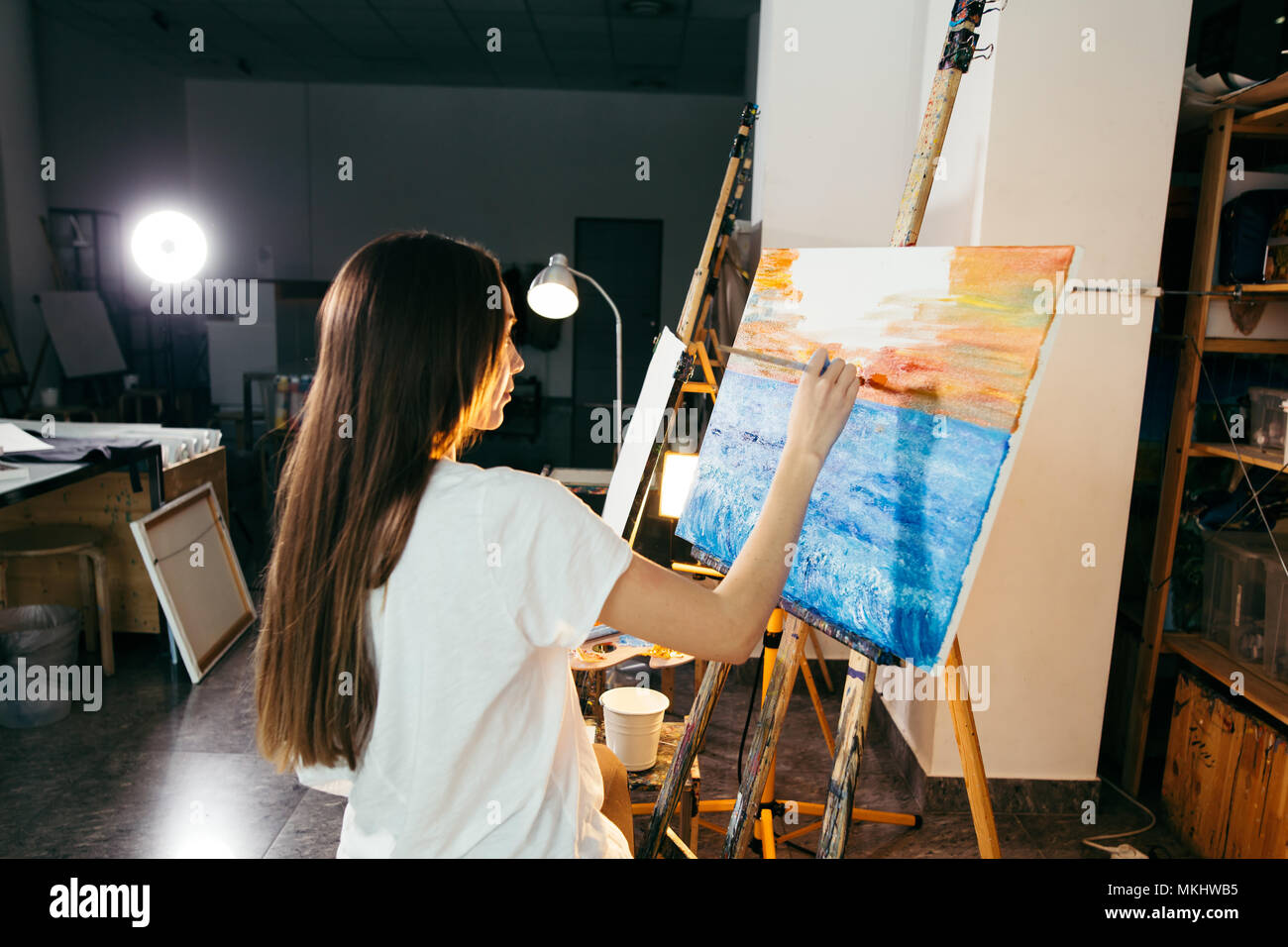 female artist paintng sea-scape on canvas with oil paints in dark workshop with flash light - Stock Image