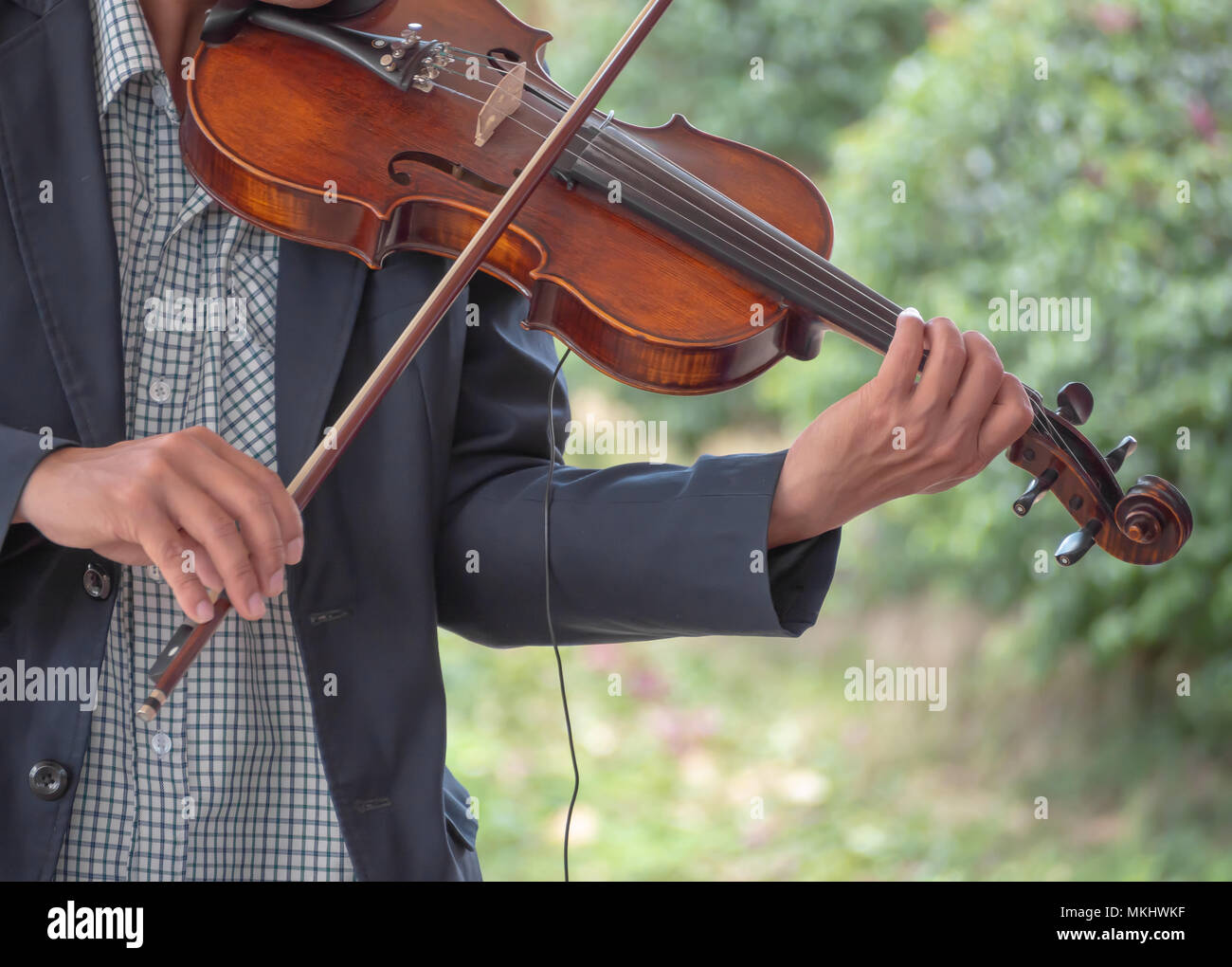 Hands of Musician Playing A Song with Violin in The Park Background - Stock Image