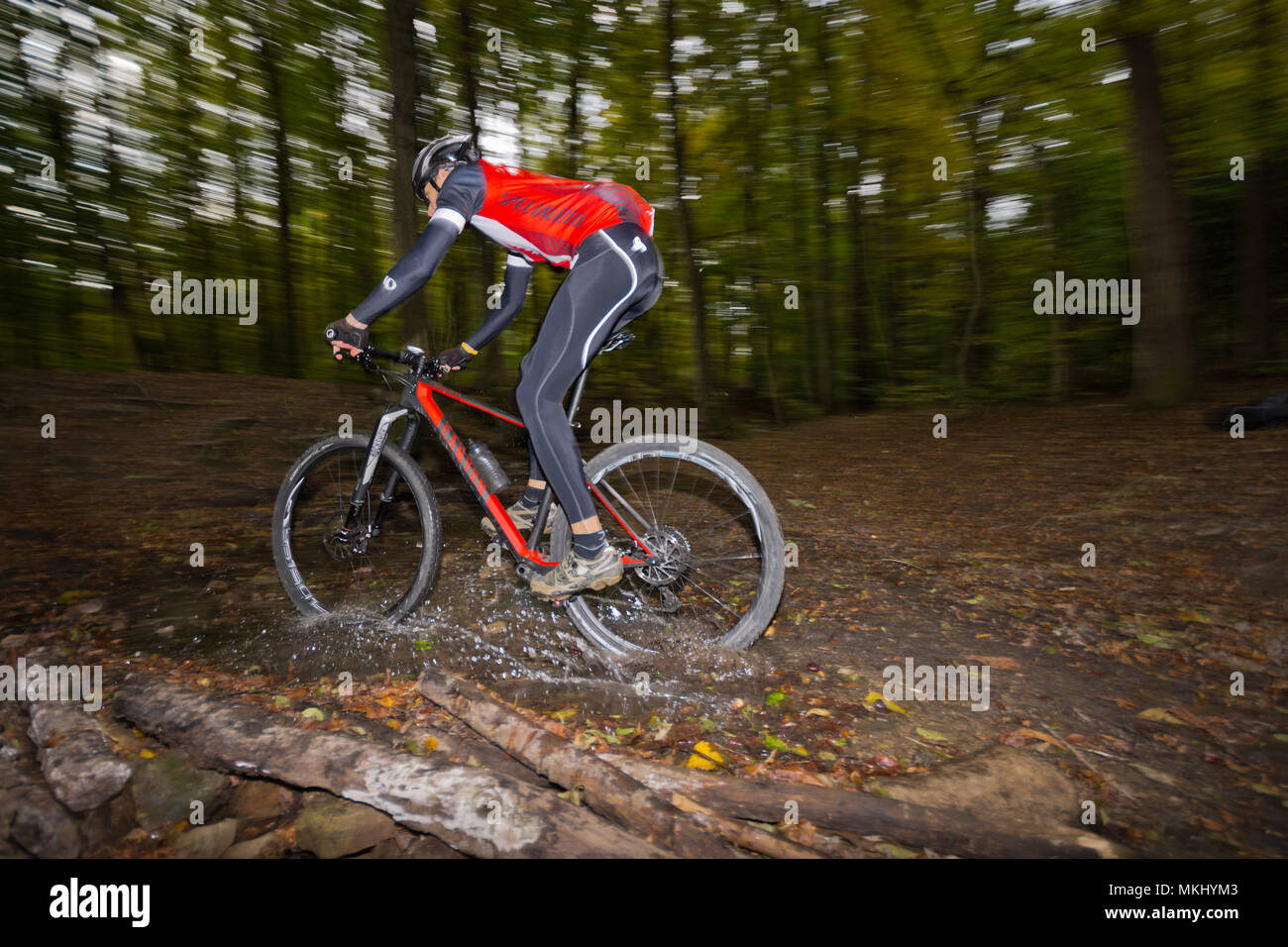 Mountainbiker in dark dusky Vienna Woods rides fast offroad on carbon hardtail along trail through forest stream with water splashes. - Stock Image
