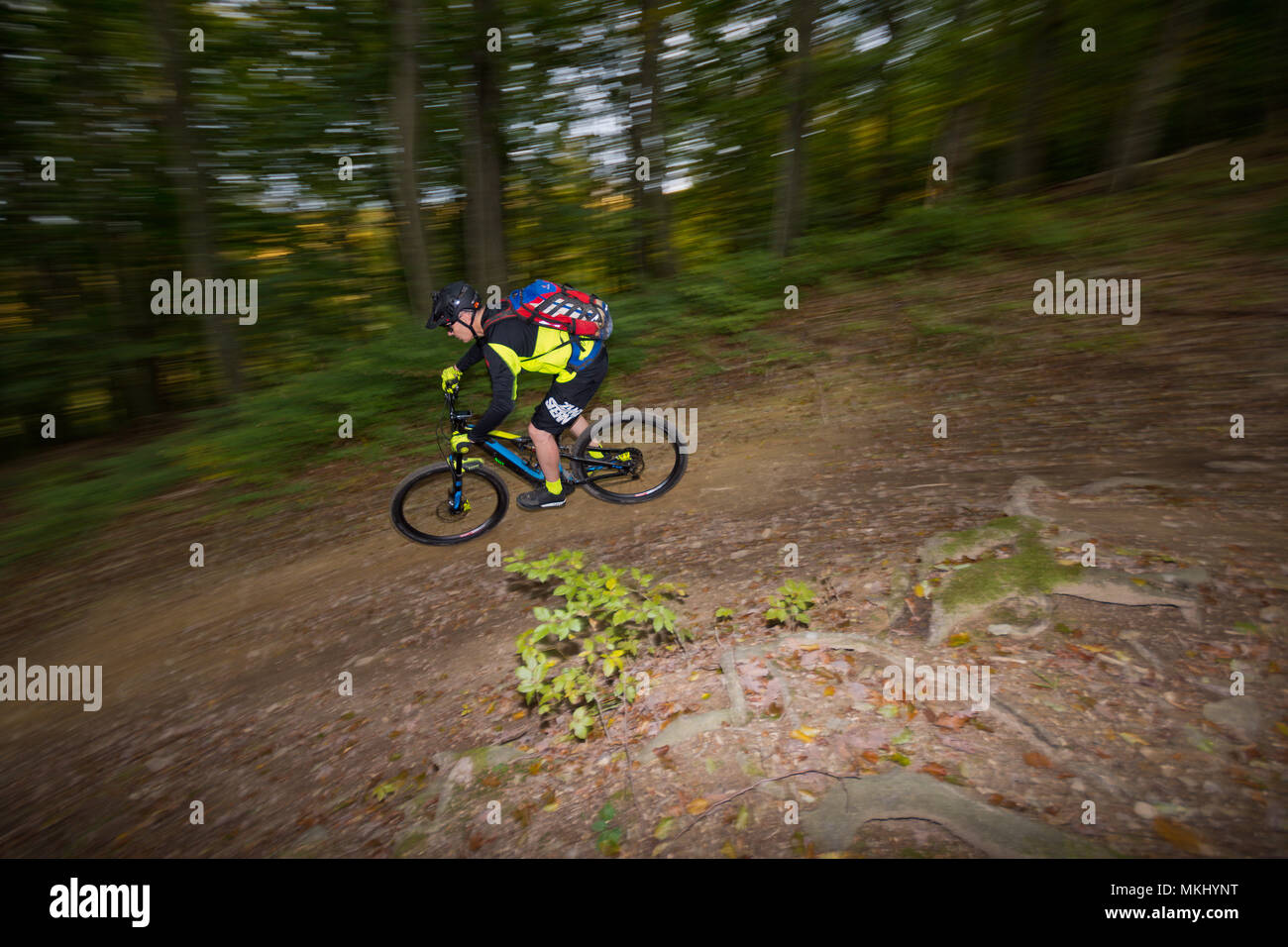 Man on e-bike in Vienna Woods rides fast along downhill trail through dark dusky autumn forest. Side view of athletic cyclist with motion blur. - Stock Image