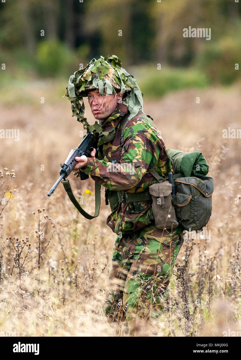1970 – 1980 British Army soldier in camouflage suit and steel helmet carrying a SLR (Self-Loading Rifle) L1A1 - calibre of 7.62 mm (Posed by Model) - Stock Image