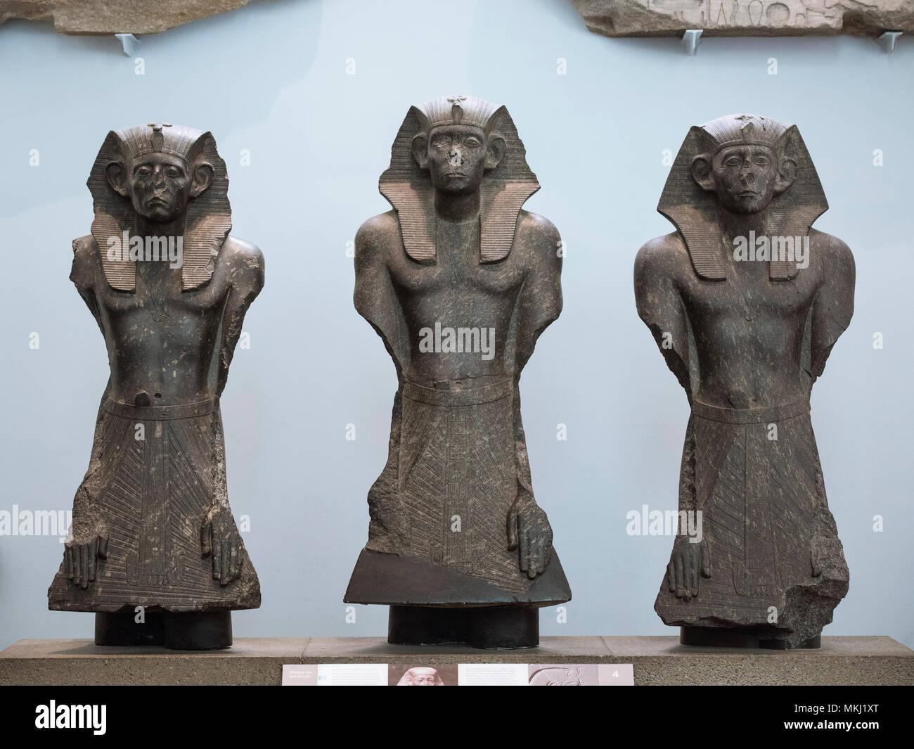 London. England. British Museum. Three statues of Egyptian Pharaoh Senwosret III (or Senusret / Sesostris), wearing a nemes head cloth, ca. 1874-1855  - Stock Image