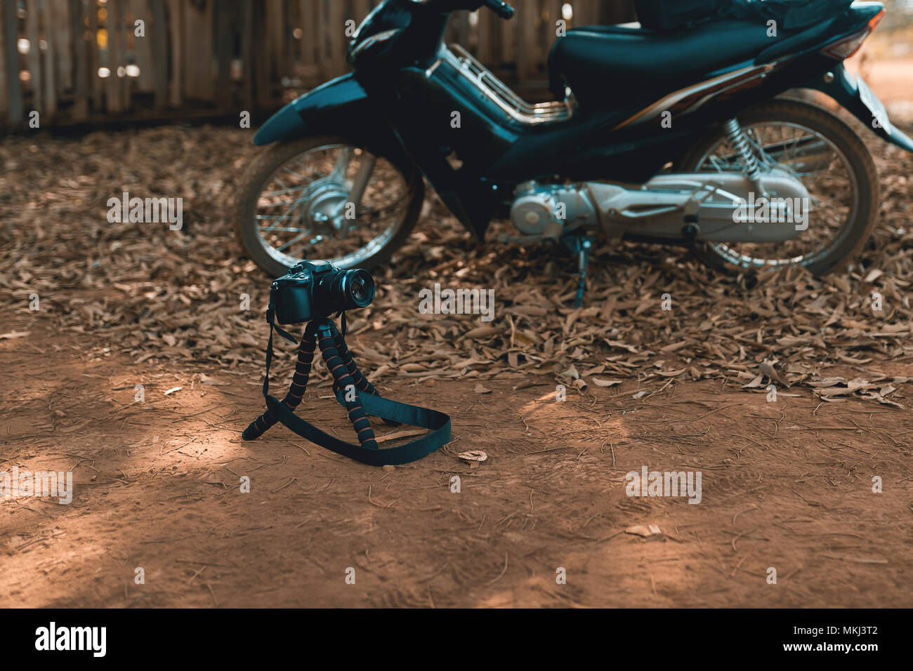 Dslr Camera Standing On Tripod At The Ground With Motorbike In The