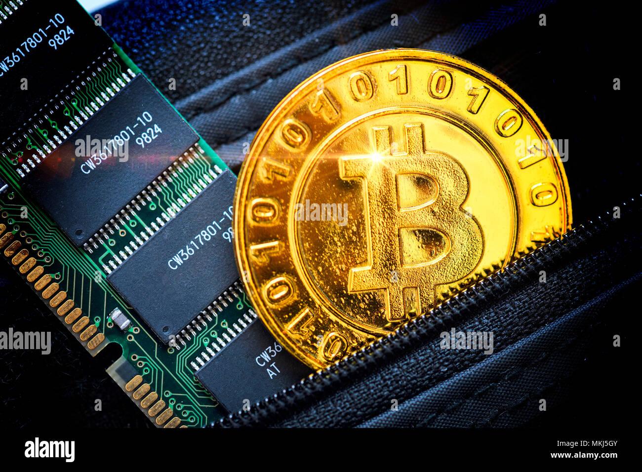 Coin with bitcoin characters and computer circuit board in a wallet, Münze mit Bitcoin-Zeichen und Computerplatine in einem Portemonnaie Stock Photo