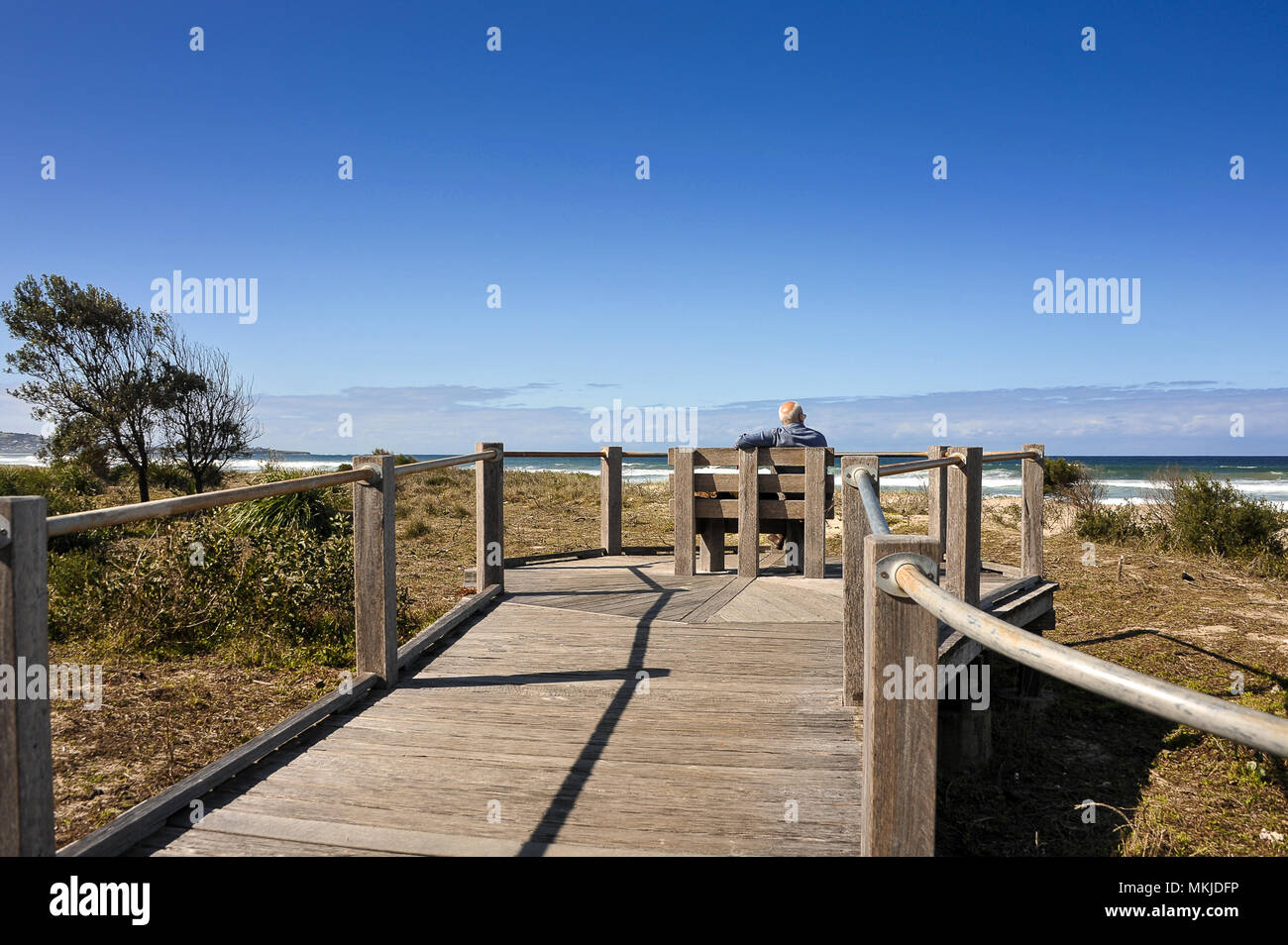 Man relaxes on wooden bench, watching the waves along Seven Mile Beach, Australia. Coastal scene, wooden boardwalk, grassy dunes and blue sky - Stock Image