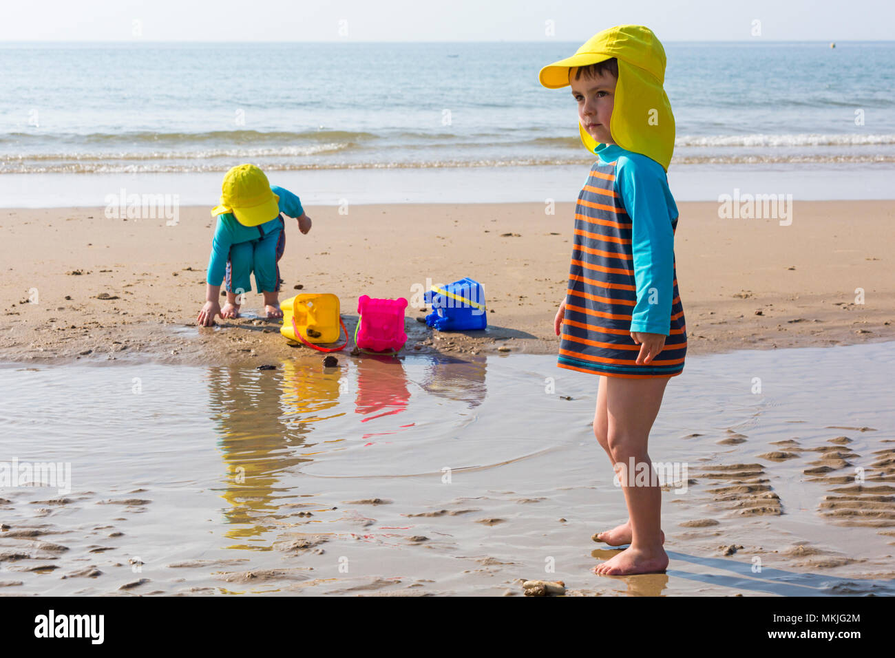 Bournemouth, Dorset, UK. 8th May 2018. UK weather: warm sunny start to the day, as two young lads (aged 4 and 2) enjoy playing at the seaside with a game of throw the shells and stones into the buckets on the seashore at Alum Chine beach. Credit: Carolyn Jenkins/Alamy Live News Stock Photo