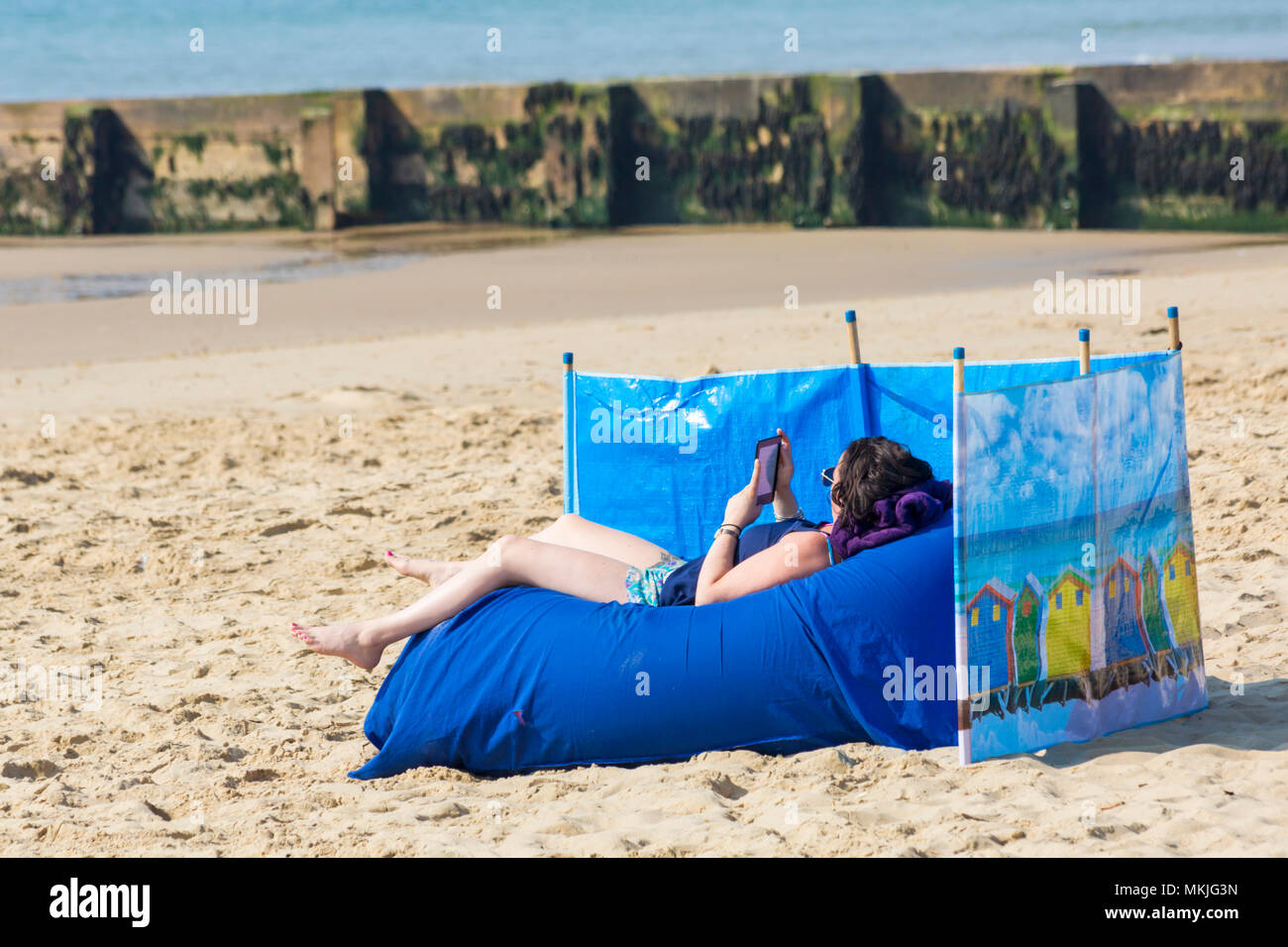 Bournemouth, Dorset, UK. 8th May 2018. UK weather: warm sunny start to the day, as a young woman relaxes on the beach at Alum Chine beach reading her kindle. Credit: Carolyn Jenkins/Alamy Live News Stock Photo