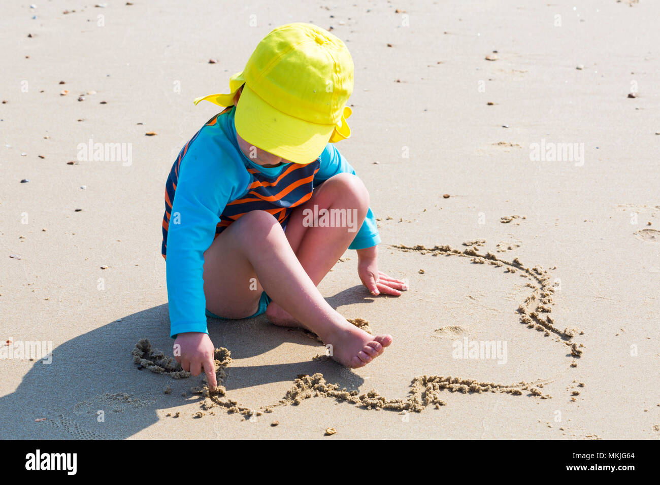Bournemouth, Dorset, UK. 8th May 2018. UK weather: warm sunny start to the day, as the a young lad (aged 4) draws in the sand with his finger at Alum Chine beach. Credit: Carolyn Jenkins/Alamy Live News Stock Photo