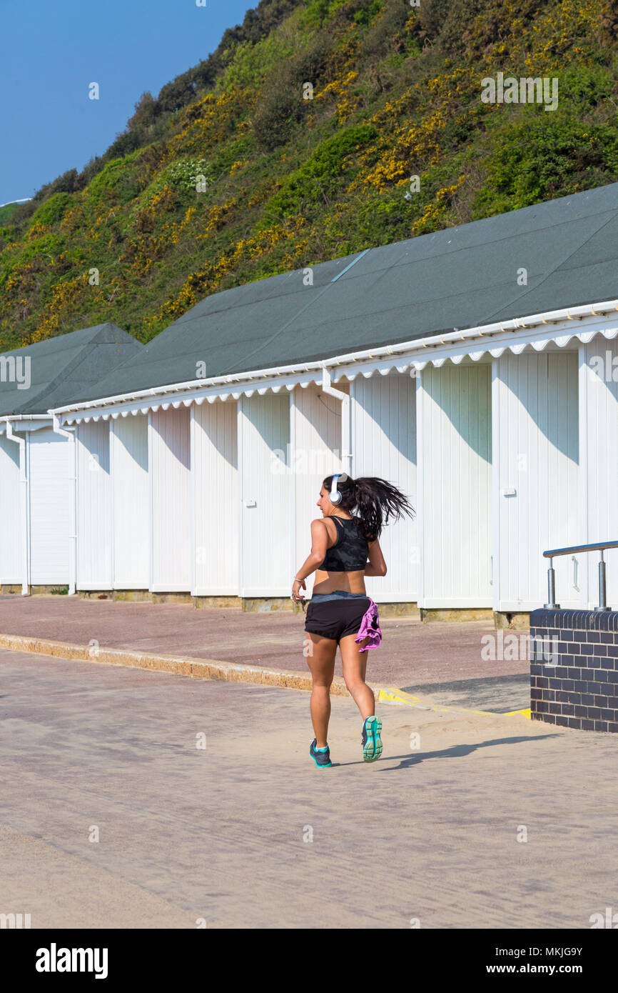 Bournemouth, Dorset, UK. 8th May 2018. UK weather: warm sunny start to the day, as a young woman jogs along promenade past beach huts. Credit: Carolyn Jenkins/Alamy Live News Stock Photo