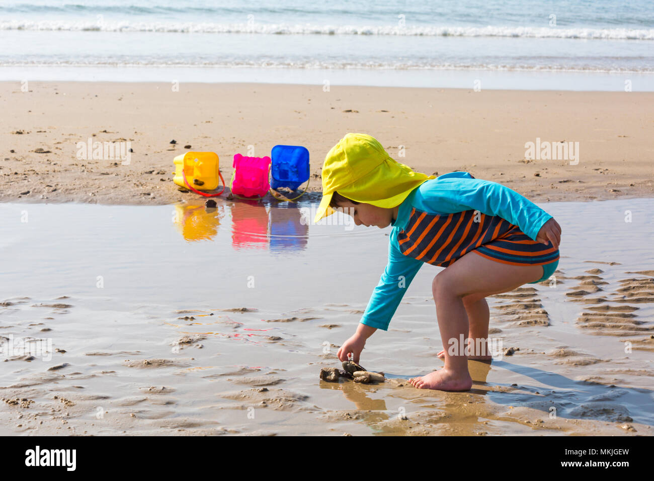 Bournemouth, Dorset, UK. 8th May 2018. UK weather: warm sunny start to the day, as a young lad (aged 4) enjoys playing at the seaside with a game of throw the stones and shells into the buckets on the seashore at Alum Chine beach. Credit: Carolyn Jenkins/Alamy Live News Stock Photo