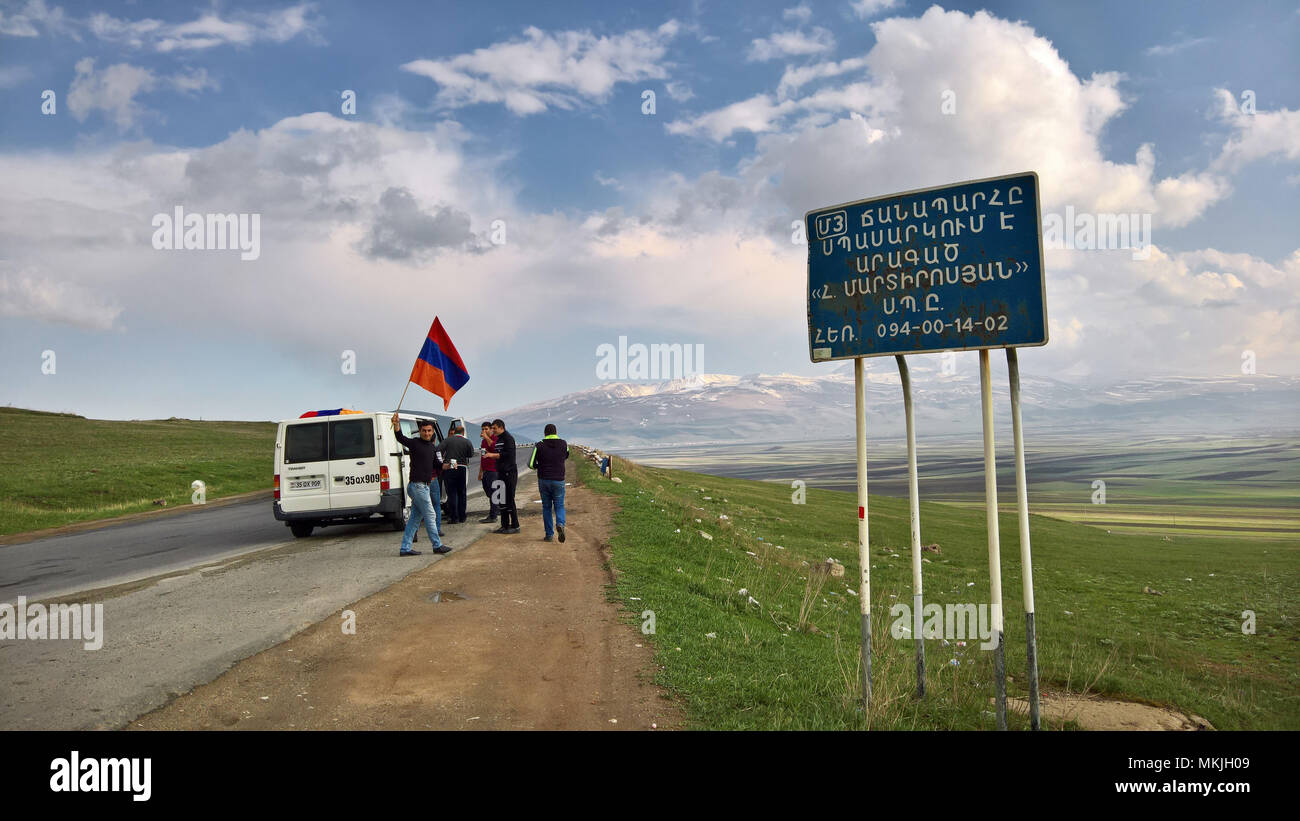 Yerevan, Armenia. 8th May, 2018. To support the rally on the eve of the possible election of opposition leader Nikol Paschinjan on May 8th, 2018, a party of friends drove from their home province Lori to the capital of Yerevan in a celebratory mood with Armenian flags waving from their mini van. Mount Aragat, Armenia's highest mountain, is in the background. Credit: zerega/Alamy Live News - Stock Image