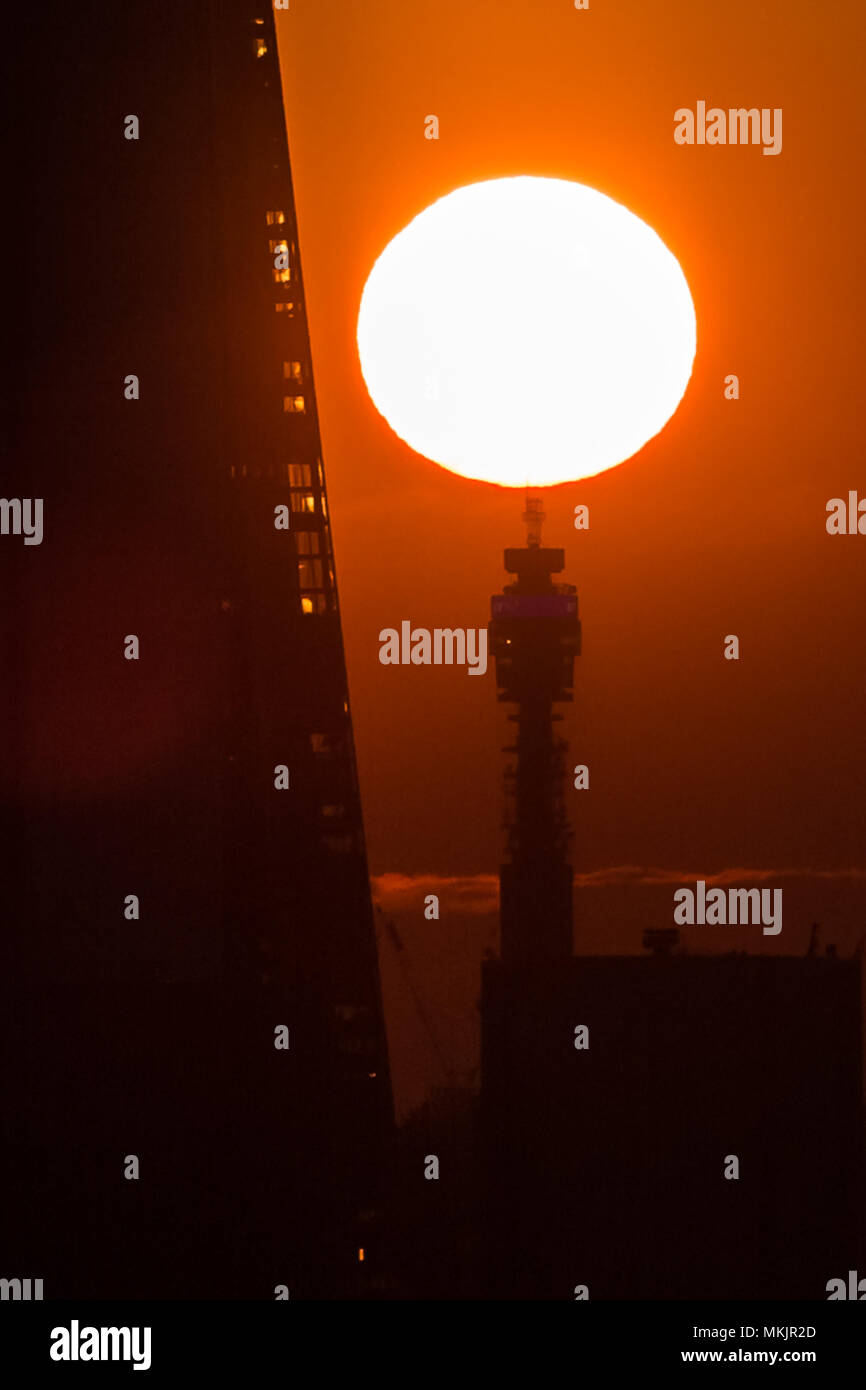 London, UK. 8th May, 2018. UK Weather: The setting sun seen over the BT tower next to The Shard skyscraper building. © Guy Corbishley/Alamy Live News - Stock Image