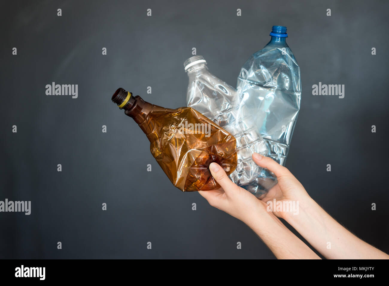 Female hand holding different types of crushed plastic bottles on black background. Recyclable waste. Recycling, reuse, garbage disposal, resources, e - Stock Image