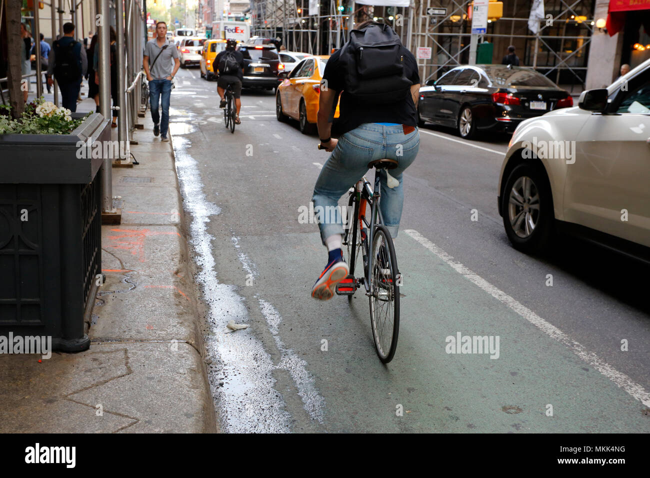 A cyclist in a bike lane, the bicycle equipped with a bike balls tail light dangling off the seat. - Stock Image
