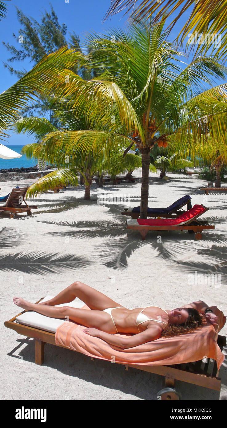 Sonnenbad unter Palmen am Strand im Hotel Hibiscus, Ort Pereybere, Nordwesten von Mauritius Stock Photo