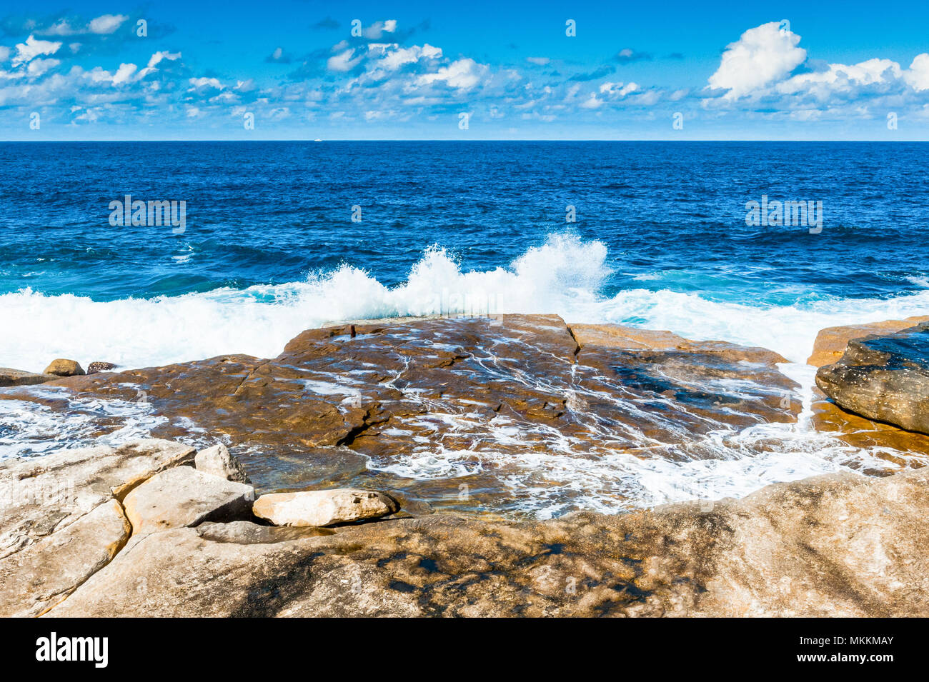 The stunning views along the famous Coogee Beach walk near to Bondi Beach, New South Wales, Australia. Waves crashing on the rocks with a beautiful bl Stock Photo