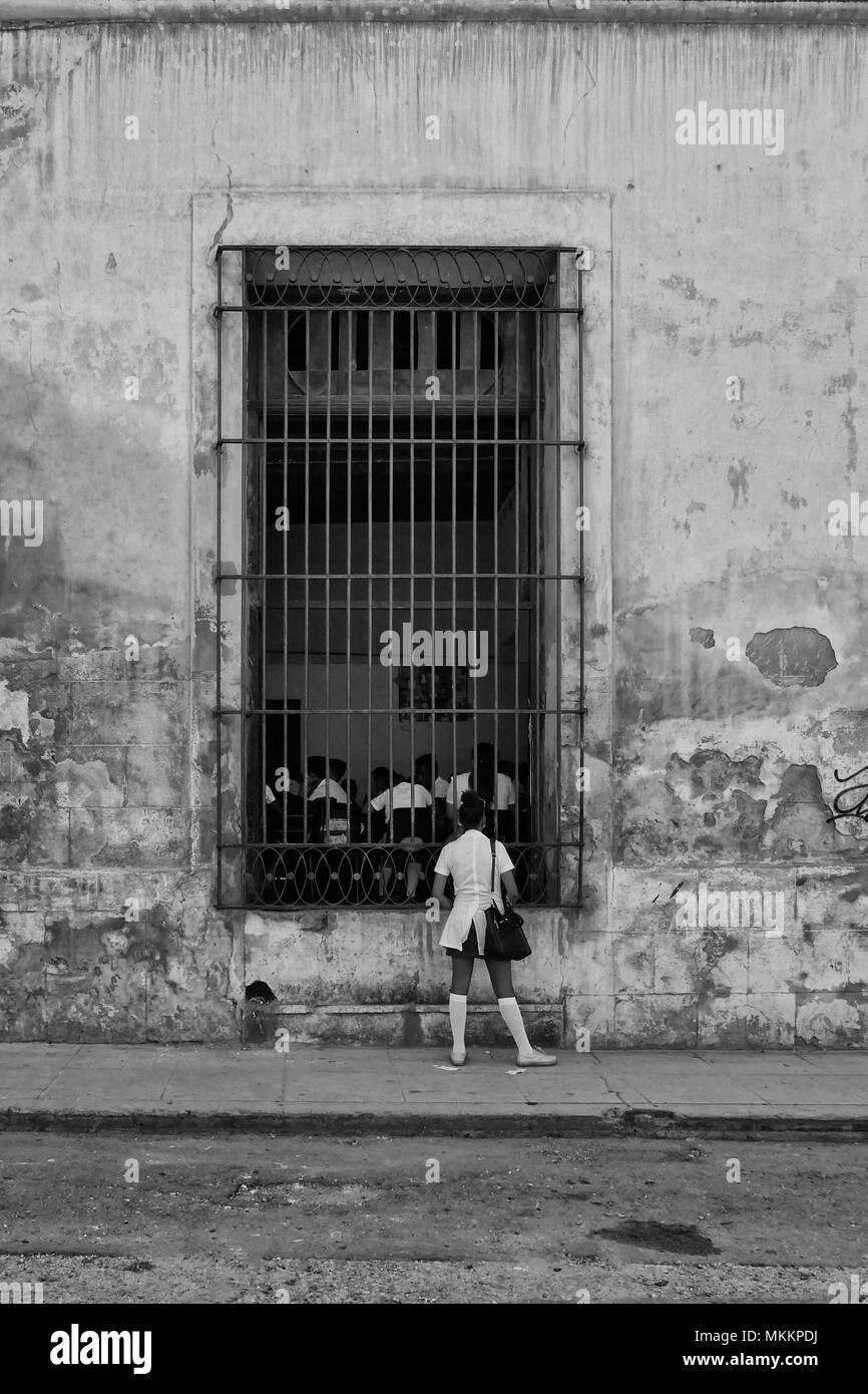 A Cuban school girl looks through a barred window onto other school pupils. Havana, Cuba - Stock Image