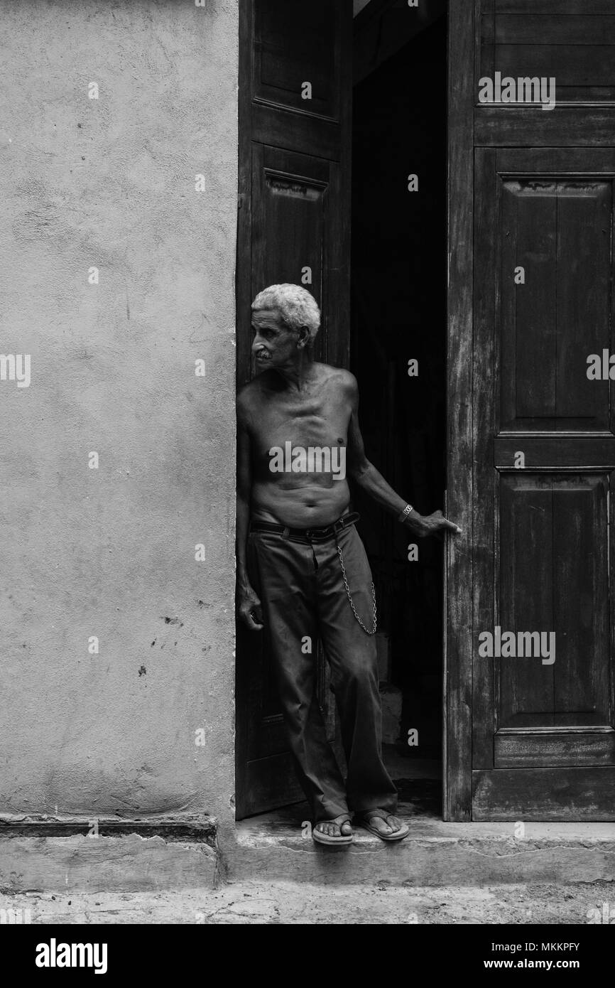 Bare chested local senior male with grey hair stands by weather worn doorway, looks down an urban street, Havana, Cuba, Caribbean - Stock Image