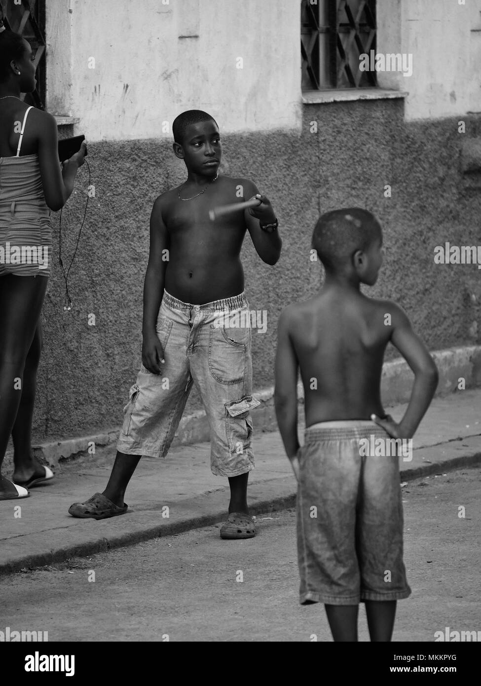 Black and white photograph of Afro Caribbean boys playing game of street baseball with improvised equipment, Havana, Cuba - Stock Image