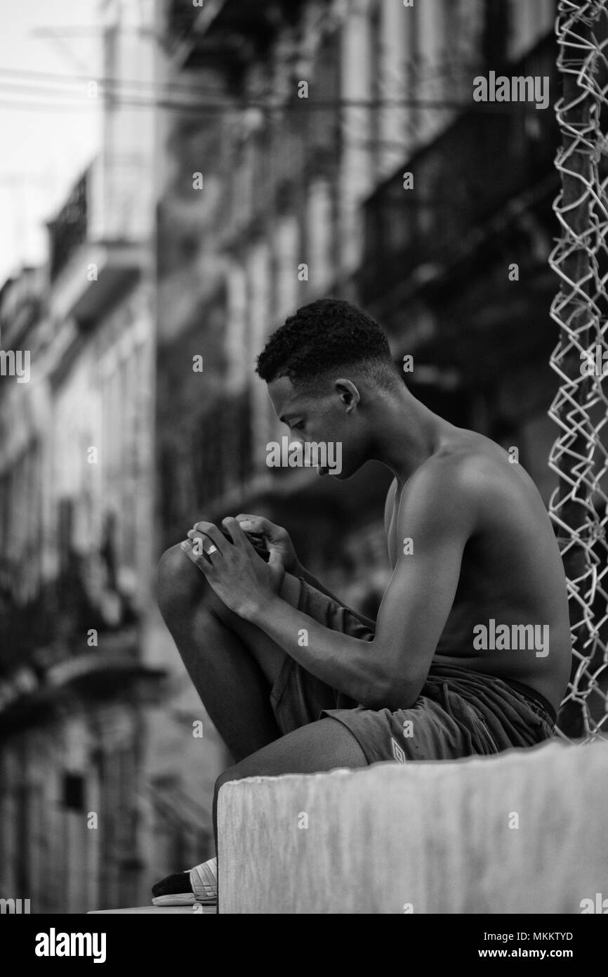 Teenage male sitting on wall checking his mobile device, Havana, Cuba - Stock Image