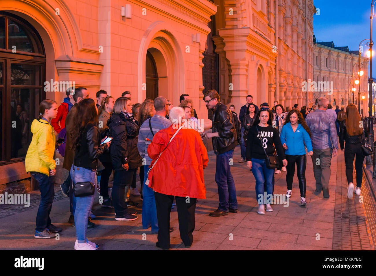 MOSCOW, RUSSIA - APRIL 30, 2018: A guide with a group of tourists near St. Basil's Cathedral on Red Square. Evening, dusk before sunset. - Stock Image